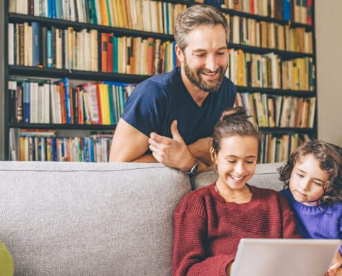 Father and two daughter looking at the tablet and smiling.