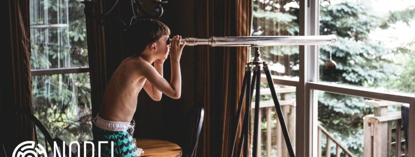Young boy standing on a chair and looking through a telescope.