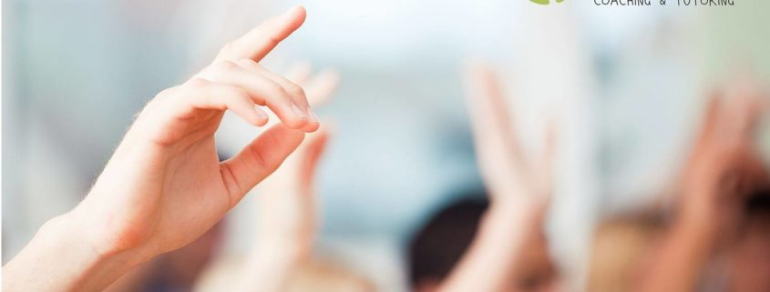 Children raising hands in a classroom.
