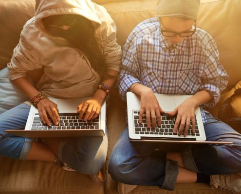 Boy and a girl sitting on a bed with their laptops.