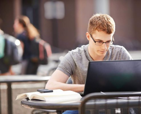 Teenage boy sitting outside in front of his laptop.