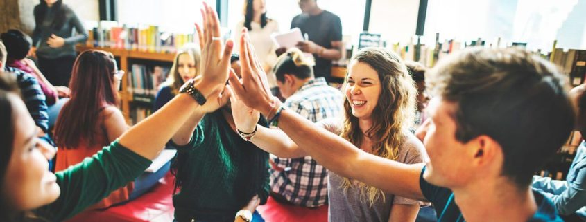 Four teenagers stand in the middle of the classroom or a work room of a sort, smiling and high fiveing each other.