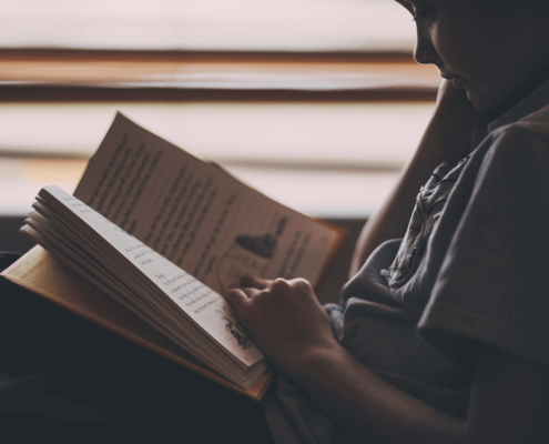 Young boy sitting and reading.