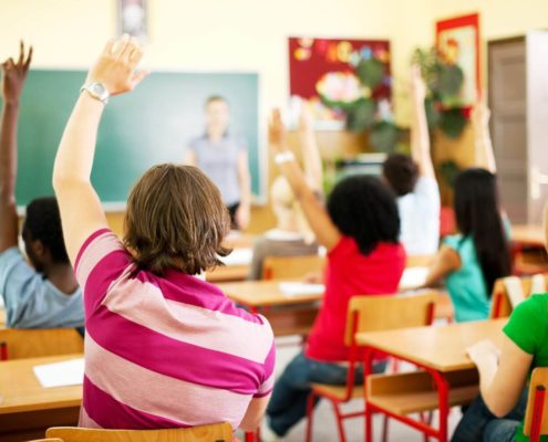 Students in the classroom raising hands.