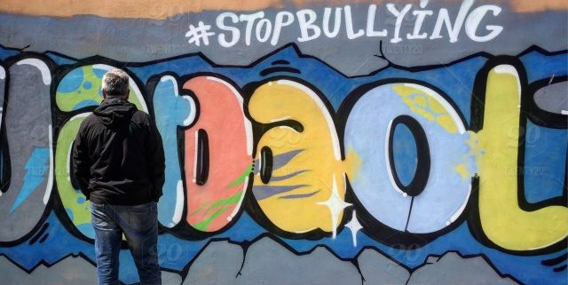 """Man standing in front of grafitti that says """"#stopbullying""""."""
