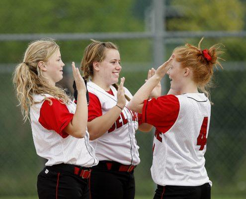 Three girls in softball uniforms celebrating on the field.