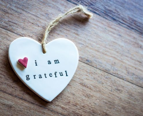 "A small clay heart with words ""I am grateful"" on it."