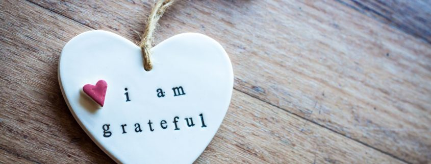 """A small clay heart with words """"I am grateful"""" on it."""