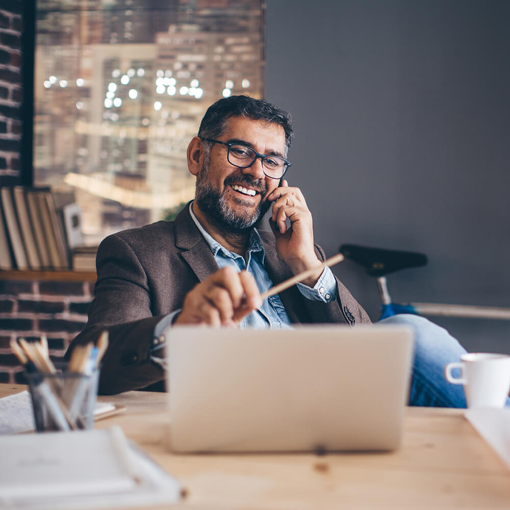 Man talking on the phone at home and smiling.