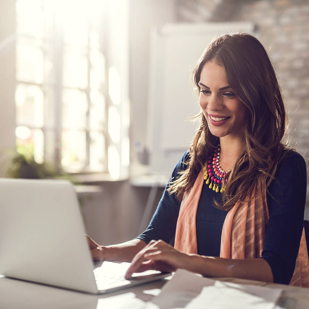 Woman looking at her laptop and smiling.