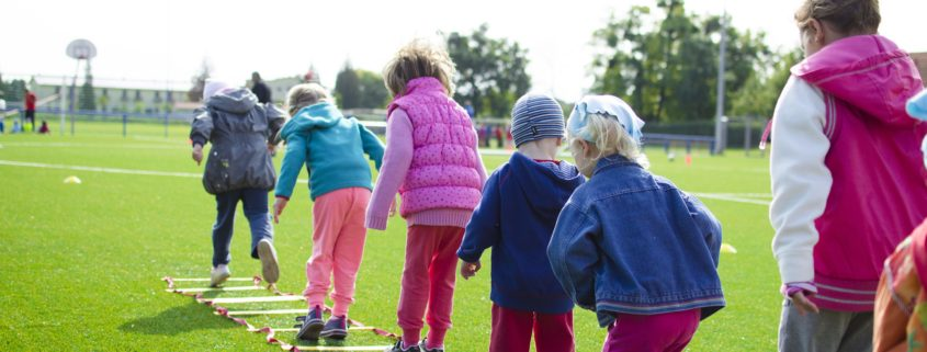 Five children are jumping on a grass in a line,, they are all wearing jackets and it is a sunny day, they are all turned with their backs against camera.