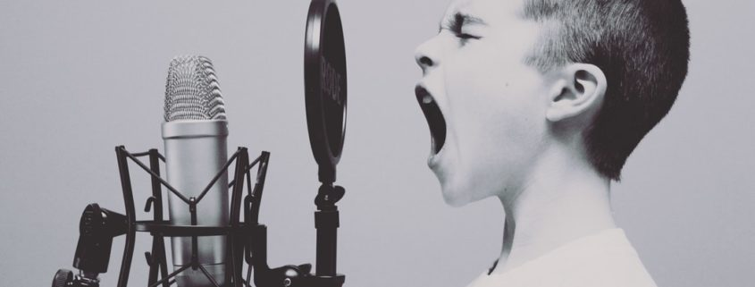 Young boy shouting at a microphone.