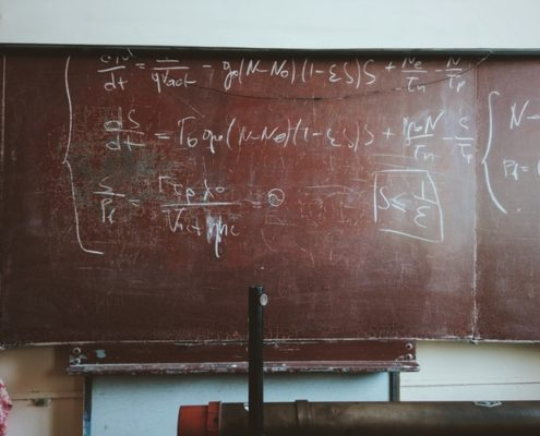 Blackboard with mathematical equation on it.