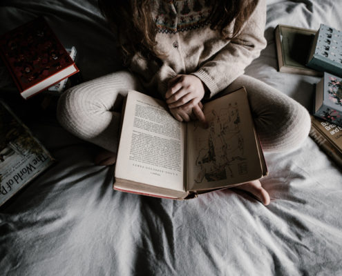 A girl sitting cross legged on her bed and reading surrounded by books.