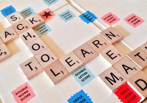"Scrabble pieces spelling ""back to school"", ""learn math"", ""read"", ""abc""."