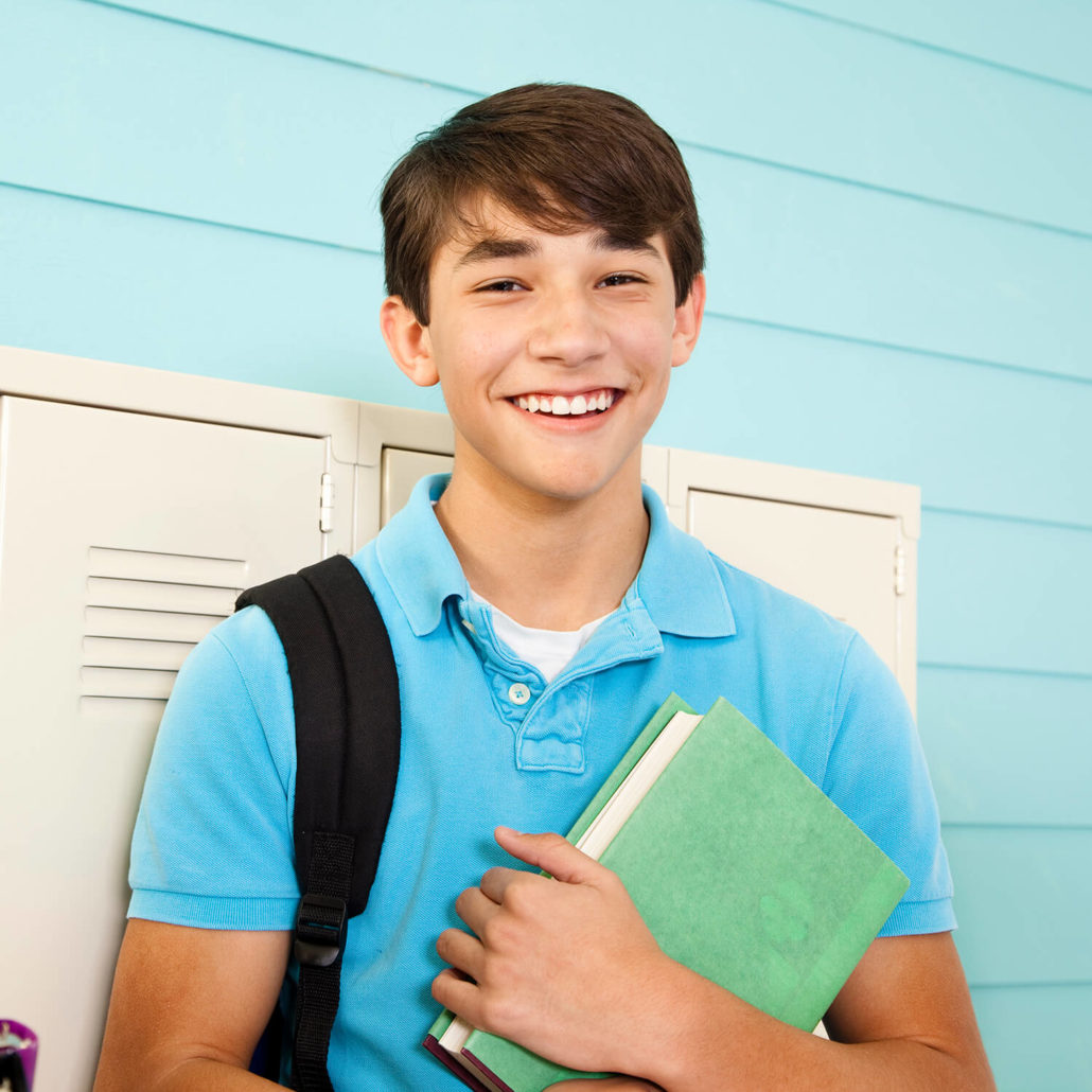 A boy holding a book next to his locker and smiling.