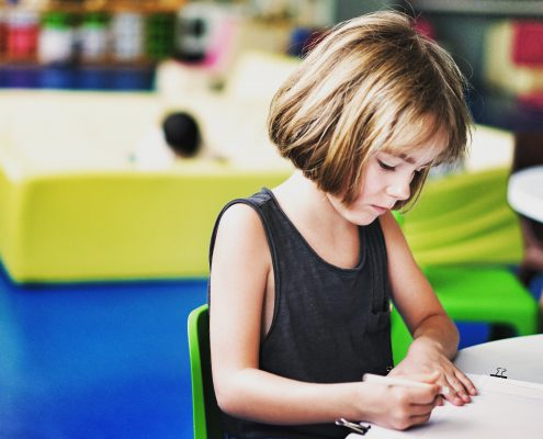 Young girl with a pen in her hand sitting at a desk.