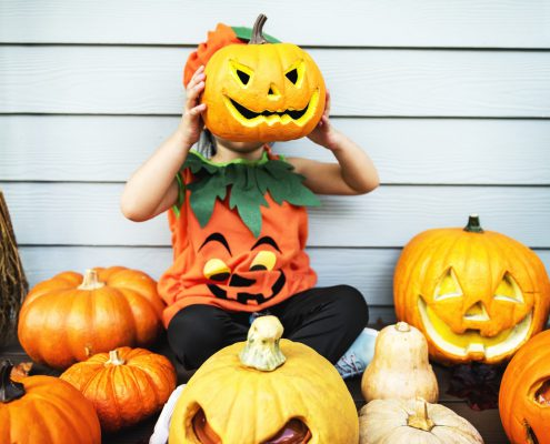 Child sitting among pumpkins shaped like faces.