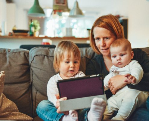 Mother sitting on a couch, with two children in her lap, looking at a tablet.