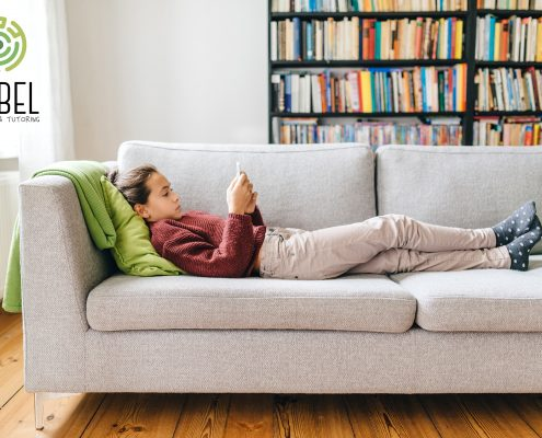 Teenager relaxing on sofa with mobile phone