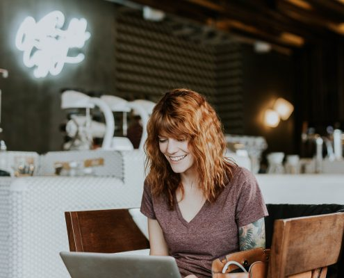 Girl smiling while looking at laptop
