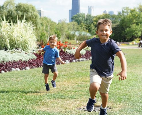 Two boys running through a field.
