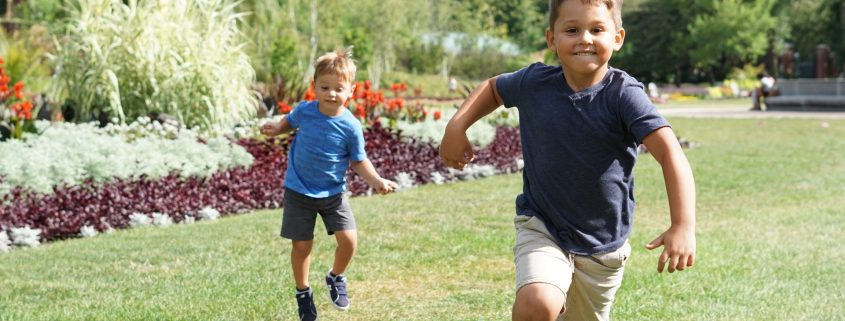 Two boys running through a field.