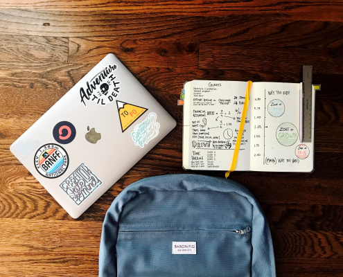 Laptop, notebook, and a schoolbag on a desk.
