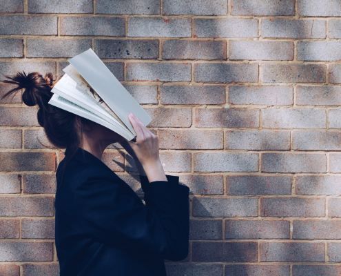 Frustrated girl holding a textbook over her head.